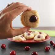 hand holding a mini vegan Danish with a cherry in the middle
