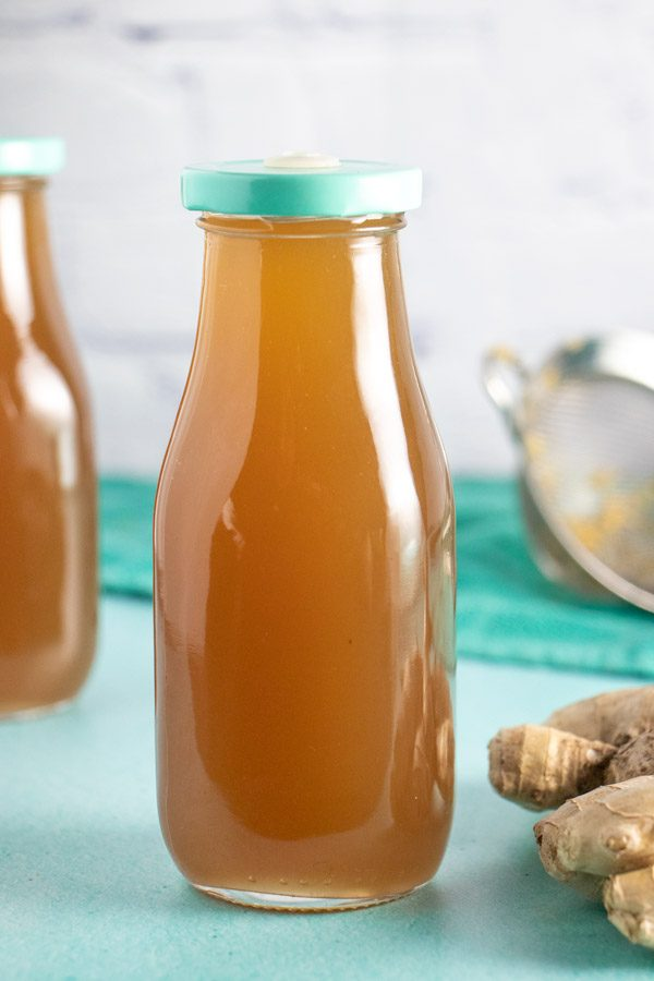 bottle of homemade ginger syrup on a blue table with strainer and ginger in the background