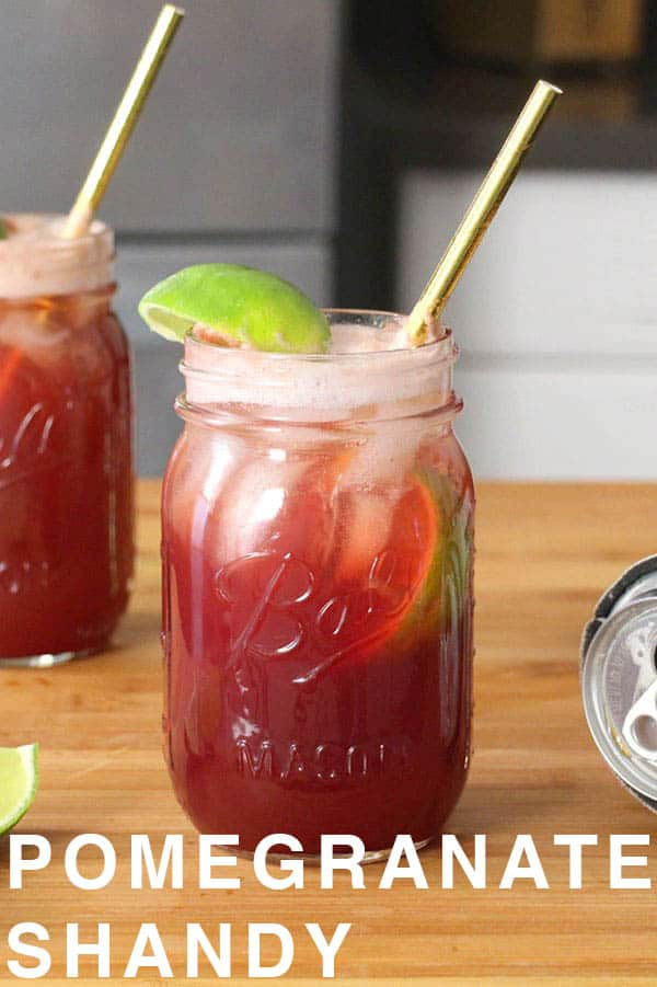 mason jars of Pomegranate Shandy on a wooden tabletop