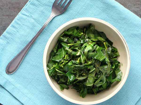 Vegan Stovetop Collard Greens heaped into a bowl on a blue napkin with a fork.