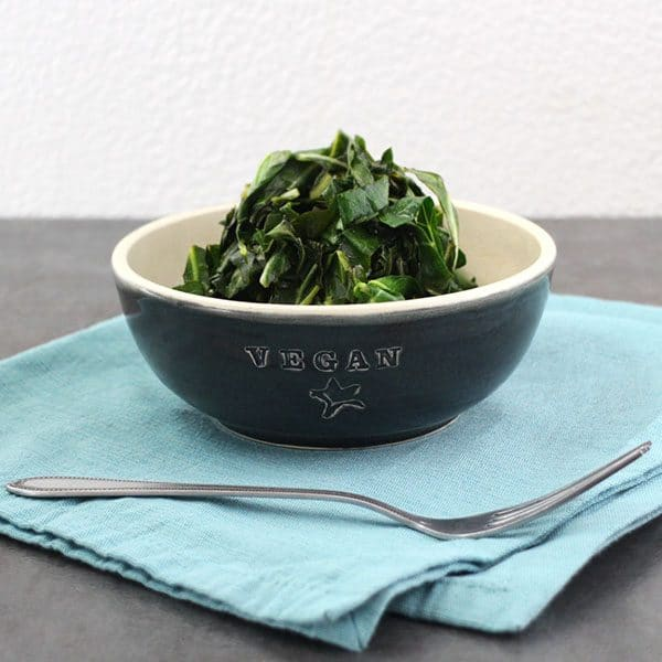 Vegan Stovetop Collard Greens in a black bowl on a blue napkin with a fork.