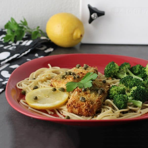 tofu piccata over spaghetti on a plate with lemon rounds and steamed broccoli