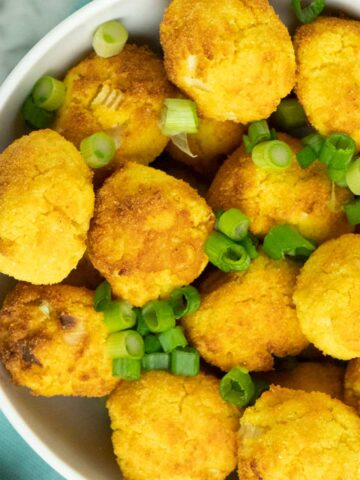 bowl of vegan air fryer hush puppies sprinkled with chopped green onion