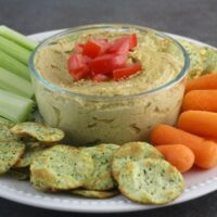 Bowl of Dilly Vegan Sunflower Seed Dip with carrots, celery, and crackers
