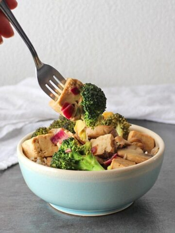 Bowl of Baked Tofu Stir Fry with fork taking a bit bite.