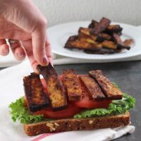 hand placing a piece of tofu bacon onto a vegan BLT