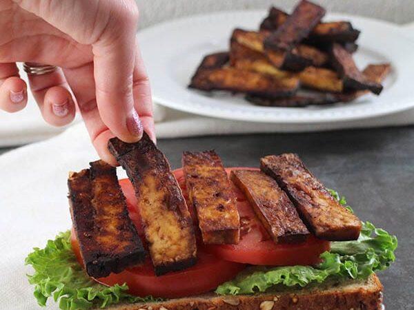 hand placing a piece of tofu bacon onto a vegan BLT