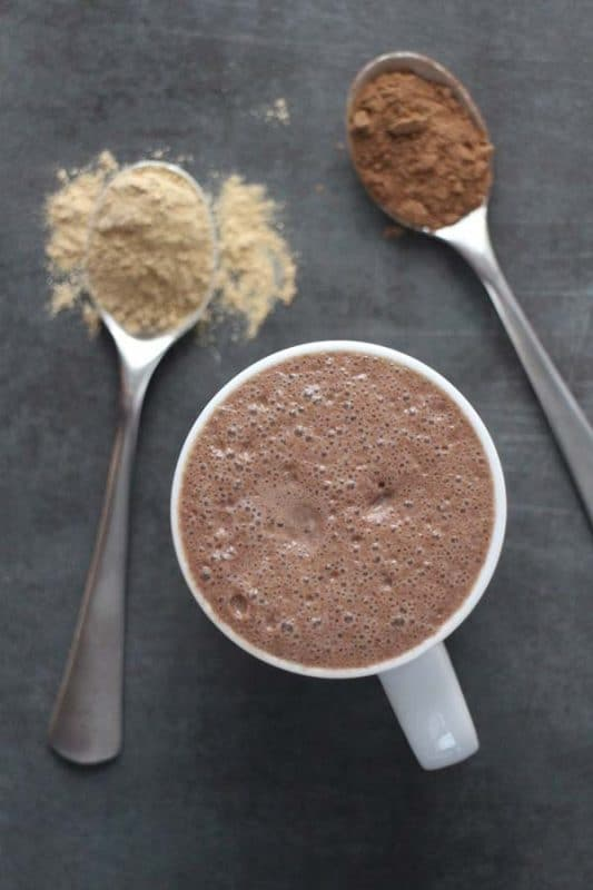close-up  of maca latte with spoons of maca powder and cocoa powder next to it