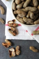 Pressure Cooker Boiled Peanuts in a bowl with boiled peanuts scattered on the table