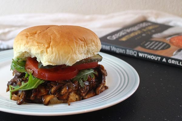 vegan pulled pork sandwich on a plate with the cookbook in the background