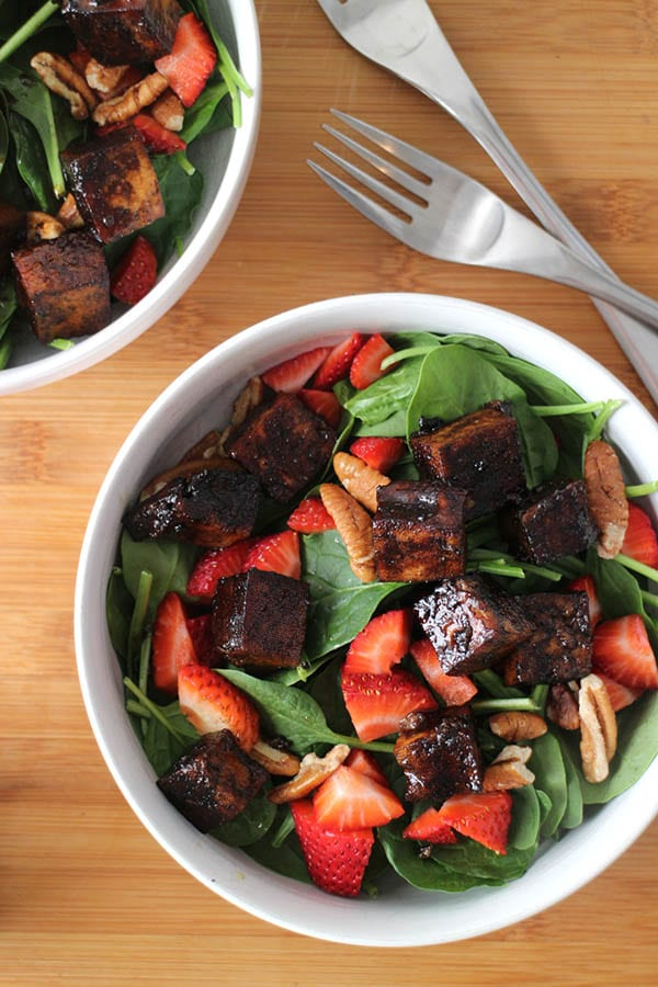 overhead photo of strawberry spinach salad with maple balsamic tofu in a white bowl