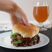 hand picking up a vegan BBQ sandwich
