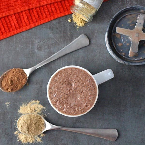 overhead photo of maca latte with spoons of maca powder and cocoa powder next to it