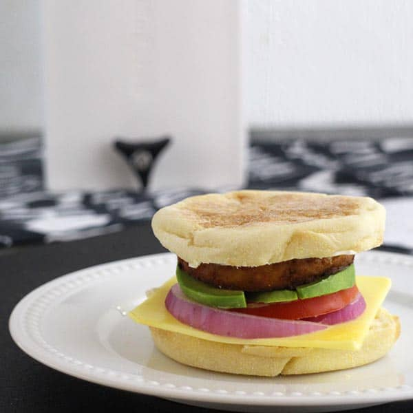 vegan breakfast sandwich on a plate with the EZ Tofu Press in the background