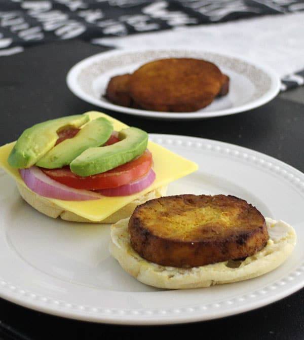 "breakfast sandwich sits open on a plate, so you can see the tofu ""egg"" and the toppings"