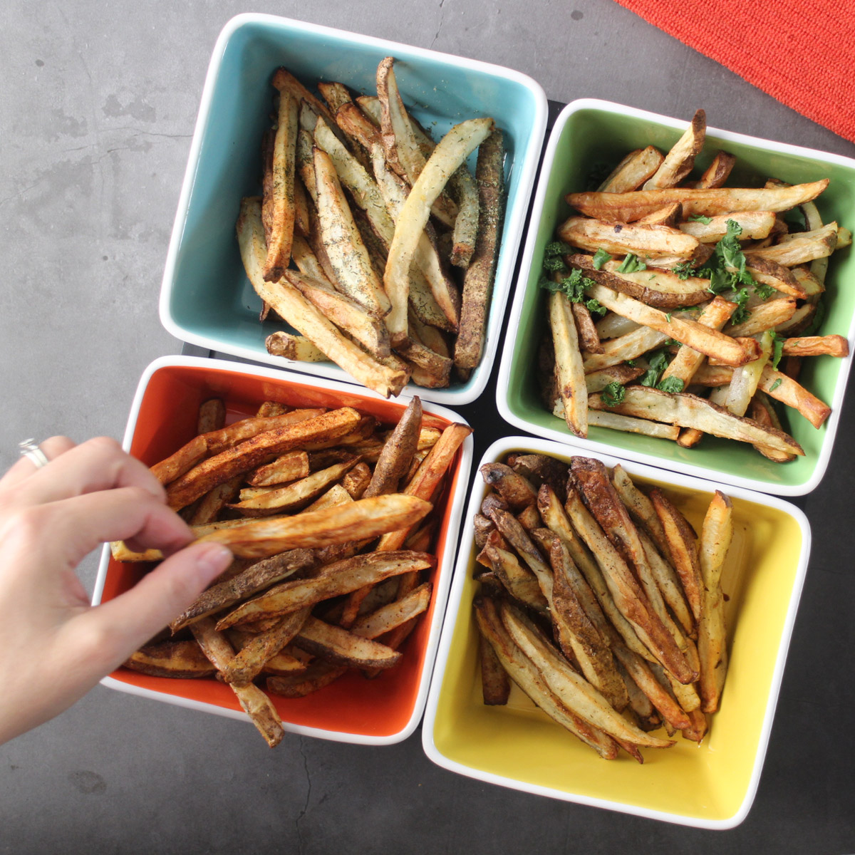 hand picking up a fry from a tray of seasoned air fryer french fries