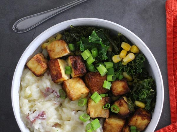 overhead photo of a vegan mashed potato bowl with tofu, kale, corn, and green onions