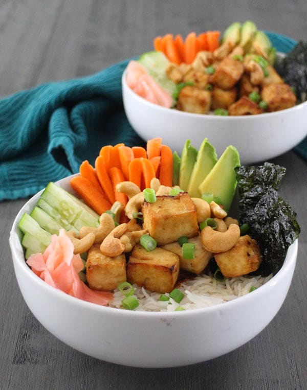 close-up of a vegan sushi bowl with tofu, carrots, pickled ginger, seaweed, cucumber, avocado, and cashews