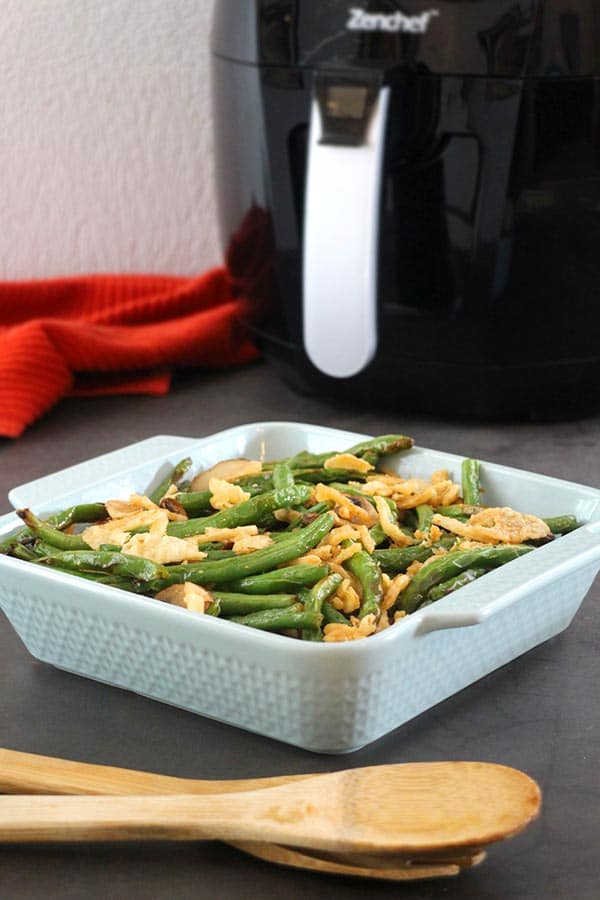 "air fryer green bean ""casserole"" in a blue baking dish with air fryer in the background"