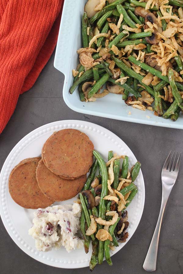 overhead shot of a holiday plate with mashed potatoes, vegan roast, and air fryer green beans and mushrooms