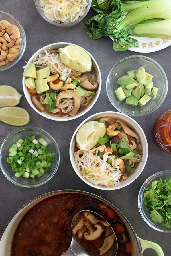 bowls of vegan ramen topped with bean sprouts, avocado, cashews, cilantro, green onion, and lime wedges