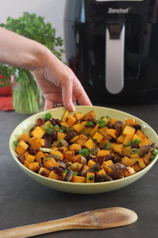 hand placing a serving bowl of air fryer roasted butternut squash on a table. Air fryer in the background