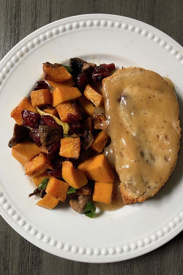 air fryer butternut squash on a plate with a vegan roast and gravy