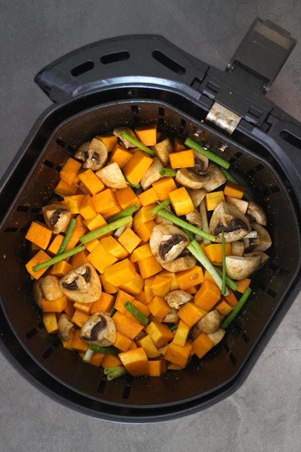 uncooked butternut squash mixture in the air fryer basket