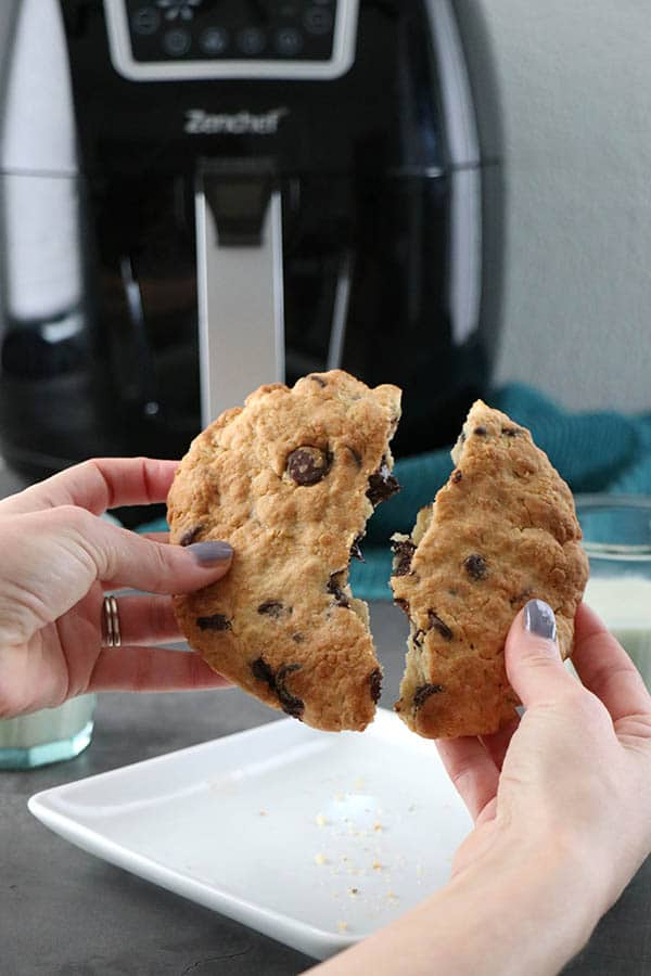 holding a chocolate chip cookie with the air fryer in the background