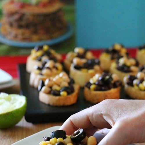 Hearty chickpeas and black beans with sweet corn and black olives make this protein-packed vegan crostini recipe super flavorful!