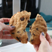 hand breaking an air fryer chocolate chip cookie in half