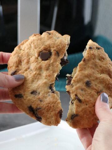 hand breaking an air fryer chocolate chip cookie in half