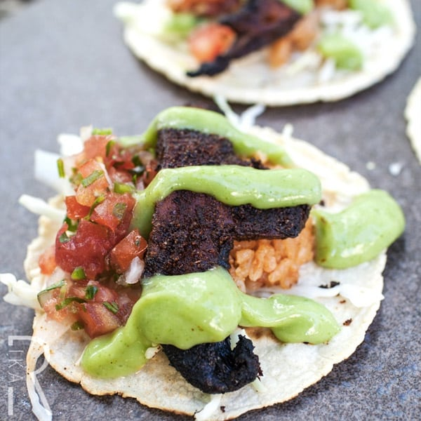 mushroom tacos with rice and salsa topped with creamy green sauce