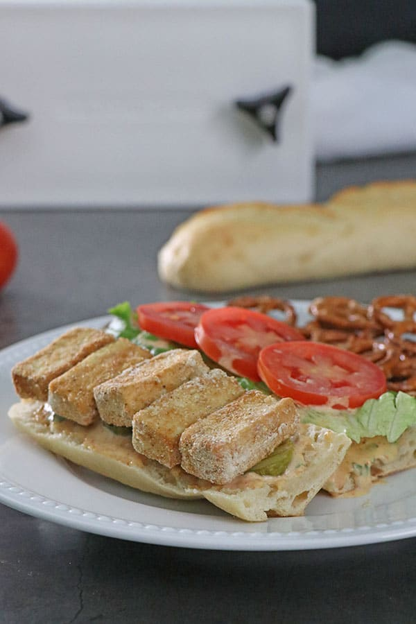 open-face vegan po' boy sandwich on a plate. Pretzels and a baguette in the background