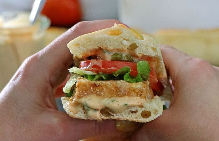 A close up of hands holding baked vegan po' boy with lettuce, tomato, and pickles