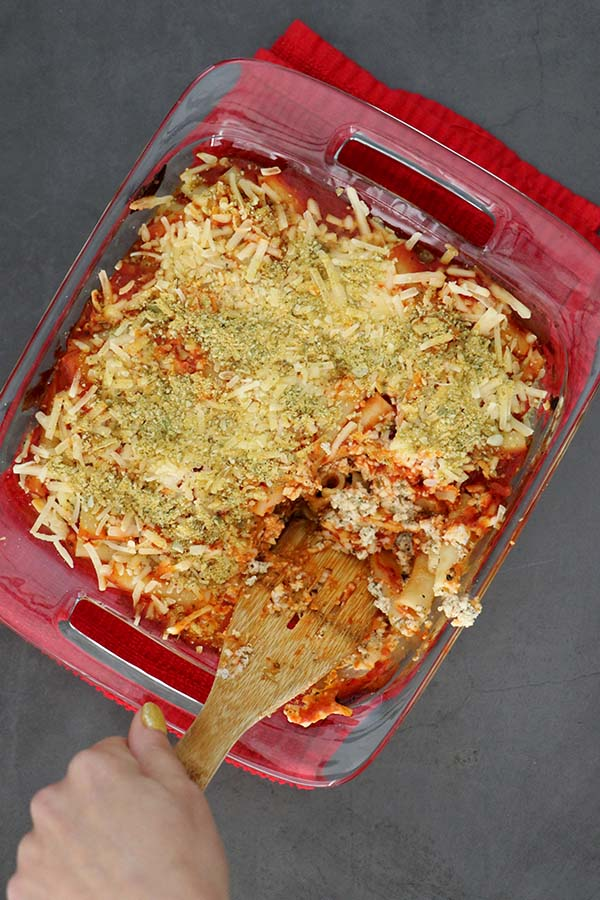 overhead view of vegan baked ziti in the pan with a spatula for serving