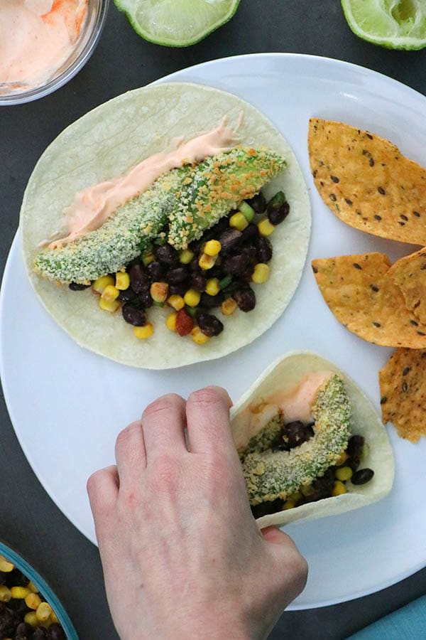 hand picking up a crispy avocado taco from a white plate with chips on the side