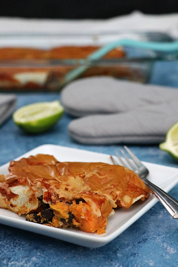 Vegan Black Bean & Sweet Enchiladas on a white plate with limes and the pan of enchiladas in the background