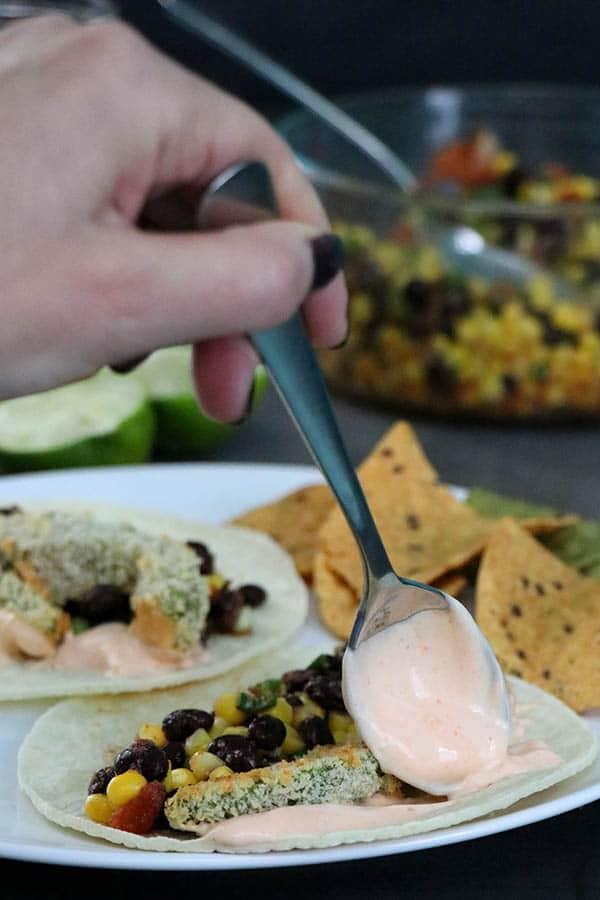spooning sriracha mayo onto a plate