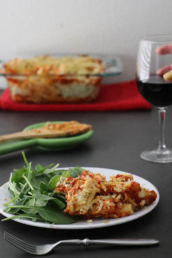 wide shot of vegan baked ziti with salad on a plate. spatula and casserole dish in the background and a hand holding a glass of red wine