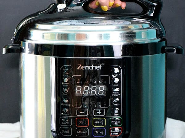 hand opening a pressure cooker lid