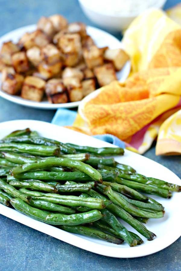 air fryer green beans next to a plate of tofu