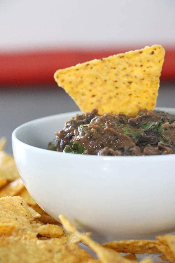 close-up of black bean dip in a bowl with a chip on top