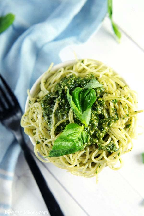 Bowl of linguini with Sarah's vegan pesto sauce garnished with fresh basil on a white table with a blue tea towel