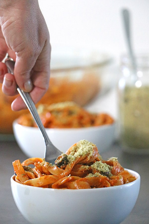 taking a bite of red pepper pesto fettuccine in a white bowl