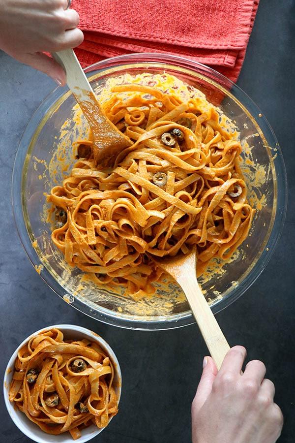 serving bowl of vegan pesto pasta with a white bowl of pasta next to it