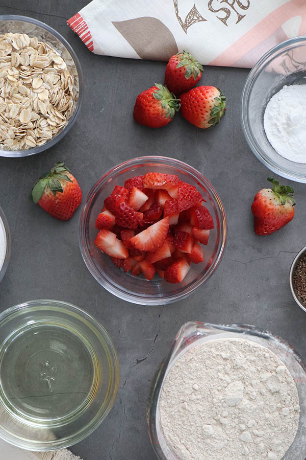 vegan strawberry muffin ingredients laid out on a slate countertop