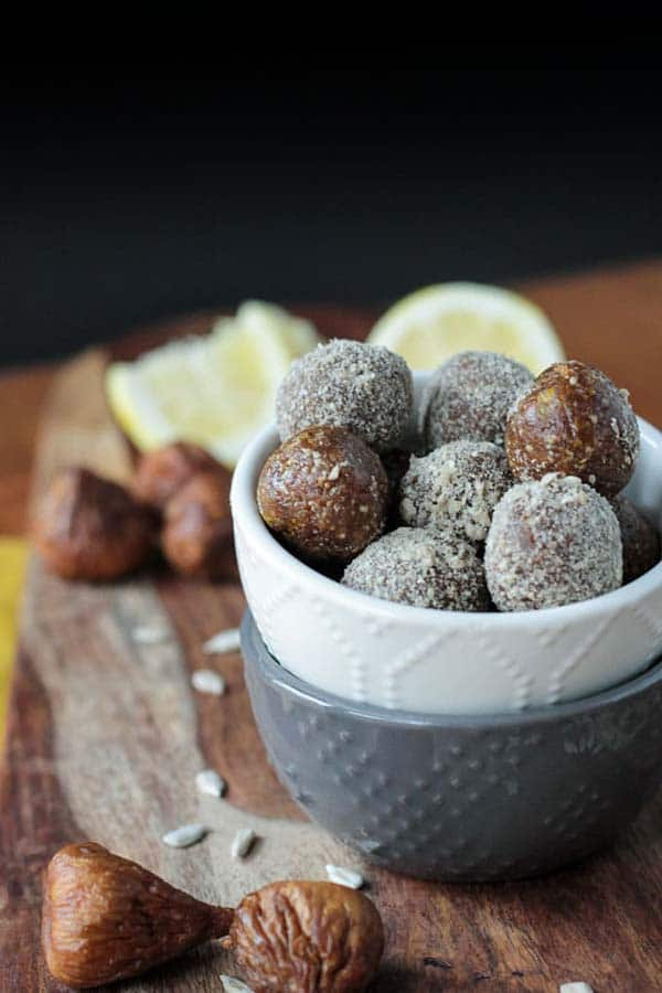 stacked bowls of Veggie Inspired's sunflower fig balls on a wooden cutting board