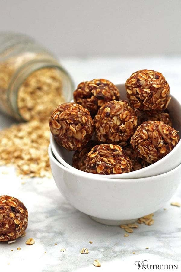white bowl of V. Nutrition's vanilla almond balls with a jar of rolled oats in the background
