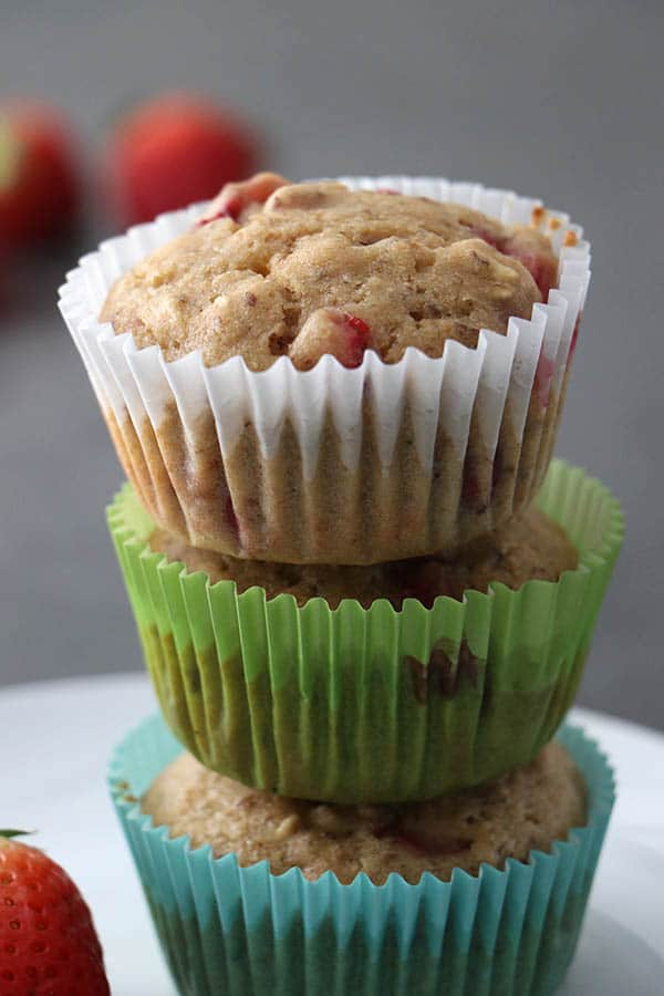 Stack of 3 vegan strawberry muffins in blue, green, and white muffin pan liners